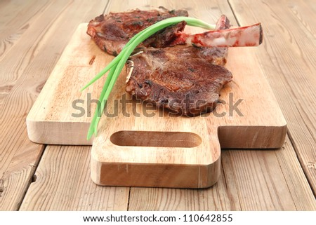 meat savory : grilled beef ribs served with green chives on wooden table - stock photo