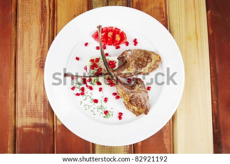 meat savory: roast veal ribs with rice garnish and pomegranate seeds on white over wood - stock photo