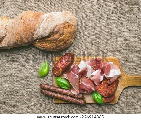 Meat selection / wine set on a rustic wood board over a rough sackcloth background - stock photo