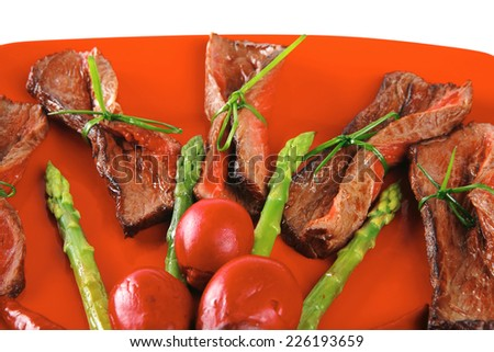 meat served on red with vegetables over white