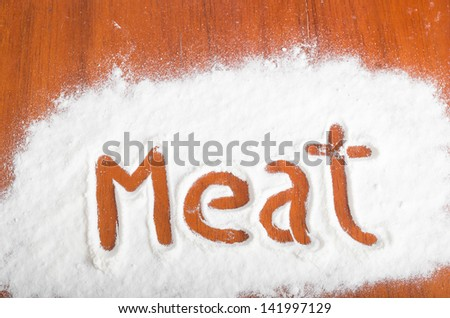 Meat sign with flour Artwork With Food And Handprints, Fun background with human handpints in scattered flour on a wooden tabletop.