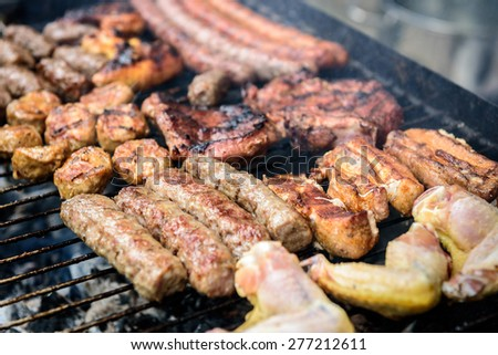 Meat skewer on barbecue grill with coal. Cevapcici, sausages, chicken wings, pork ribs and steak on charcoal barbecue BBQ.
