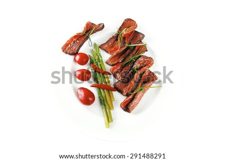meat slices on white with asparagus on plate - stock photo