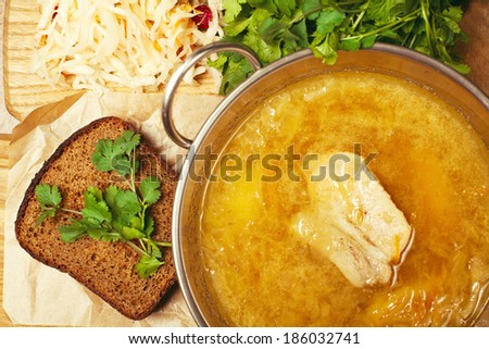 Meat soup with sour-crout (sauerkraut, cabbage), fresh parsley and a piece of dark bread on a wooden board. Close up. Indoor shot