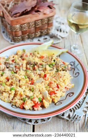 Meat Spanish paella with chicken, sausage chorrizo and Bomba rice, red peppers, tomatoes, green peas and white wine. Selective focus. - stock photo