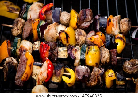 Meat spits on grill flames in background - stock photo
