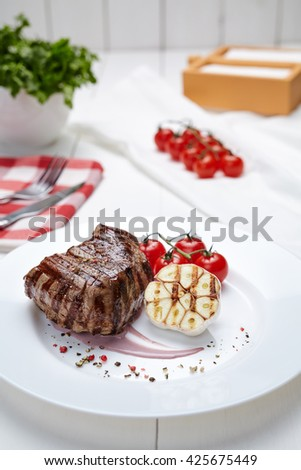 Meat steak grilled beef barbecue with garlic sauce, roast and tomatoes. Roasted fillet mignon restaurant menu meal in white plate. - stock photo