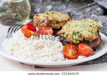Meat steak, pork fillet fried with golden cheese crust and rice - stock photo