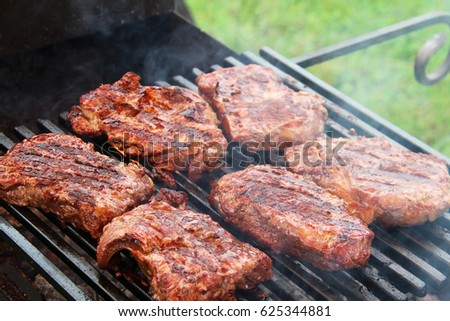 Meat steaks on the grill