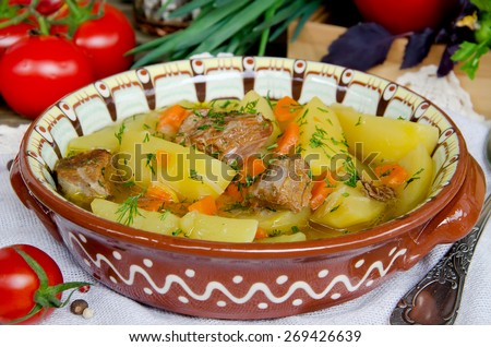 Meat stew with potatoes and vegetables on wooden table - stock photo
