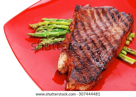 meat table : grilled beef fillet with asparagus served on red dish isolated over white - stock photo