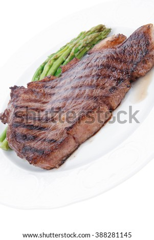 meat table : grilled beef fillet with asparagus served on white plate isolated over white