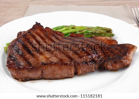 meat table : rare medium roast beef fillet with asparagus served on white plate with cutlery over wooden table