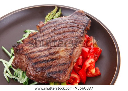 meat table : rare medium roast beef fillet with tomatoes and asparagus served on dish isolated over white - stock photo