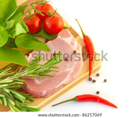 Meat, tomatoes, a basil and pepper against a wooden board - stock photo