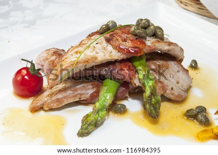 meat with asparagus on a white plate in a restaurant - stock photo