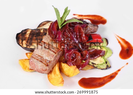 Meat with onions and vegetables in a spicy sauce on a white background. - stock photo