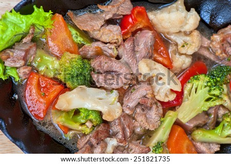 meat with vegetables at frying pan - stock photo