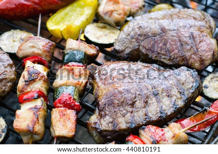 Meat with vegetables cooking on grill with flames.