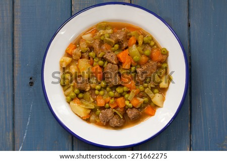 meat with vegetables in plate on blue background