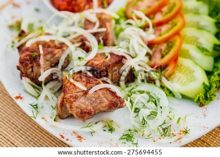 Meat with vegetables on a white plate. Restaurant - stock photo