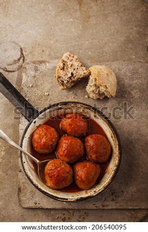 Meatballs cooked in tomato sauce in pan on grey backround - stock photo