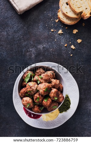 Meatballs in a cup with various sauces on a plate, grey colors