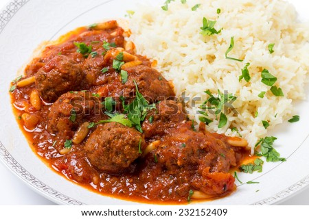 Meatballs with pine nuts in a spicy tomato sauce, a Syrian, Lebanese and Turkish speciality, sereved with rice in the traditional way - stock photo