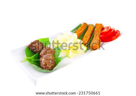 meatballs with tomatoes and lemon on basil leaf - stock photo