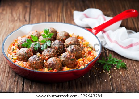 Meatballs with vegetable sauce in cast iron skillet on wooden background, selective focus - stock photo