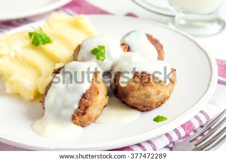 Meatballs with white creamy sauce and mash on plate close up - stock photo