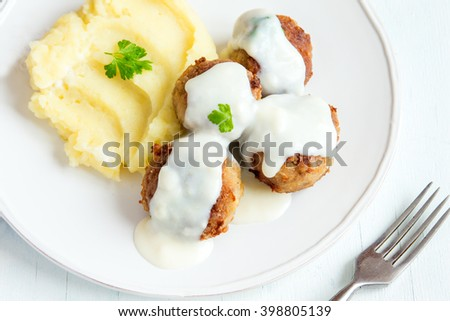 Meatballs with white creamy sauce and mash on white plate close up - stock photo