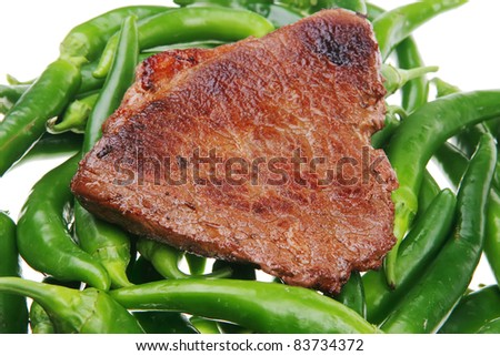 meaty food : roasted red meat steak over green hot chili peppers on a white back - stock photo