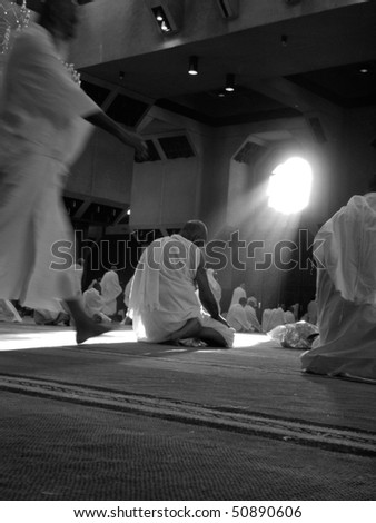MECCA - DEC 11 : Muslim pilgrims in 'ihram' clothes pray at one of the mosques Dec 11, 2007 in Mecca. 'Ihram' clothes consist of two unhemmed white clothes intended to make everyone appear the same. - stock photo