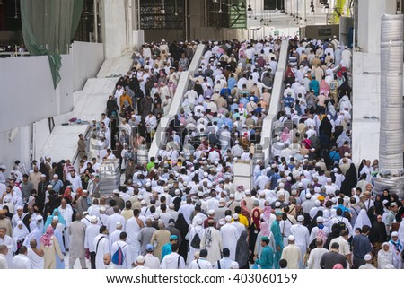 MECCA - DECEMBER 22, 2014 : Muslim pilgrims exit the mosque after prayer  in Mecca, Kingdom of Saudi Arabia. Muslims around the world face the Kaaba during prayer time. - stock photo