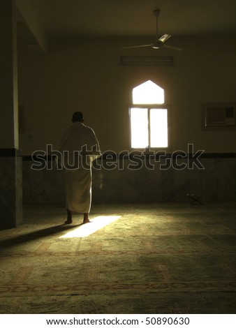 MECCA - JAN 3 : A Muslim pilgrim in 'ihram' clothes prays in one of the mosques Jan 3, 2008 in Mecca. 'Ihram' clothes consist of two unhemmed white clothes intended to make everyone appear the same. - stock photo
