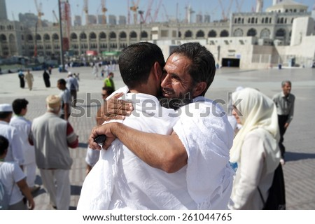 MECCA, SAUDI ARABIA - FEBRUARY 4: Two Muslims greet each other at the kaaba on February 4, 2015 in Mecca, Saudi Arabia. Muslim people praying together at holy place. - stock photo