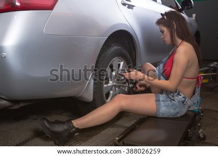 Mechanic, a young woman changing the front tire of a black sedan using a torque wrench in a tire service center garage - stock photo