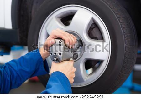 Mechanic adjusting the tire wheel at the repair garage - stock photo