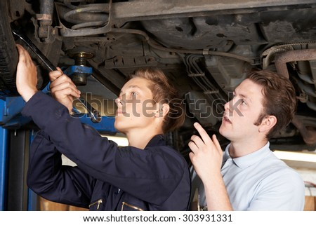 Mechanic And Apprentice Working On Car Together - stock photo