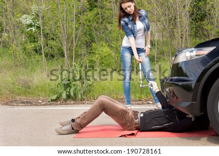 Mechanic and female driver at a roadside breakdown working as a team as she hands him the tools while he works underneath the car on a rural road - stock photo