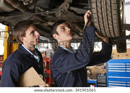 Mechanic And Trainee Working On Car Together - stock photo