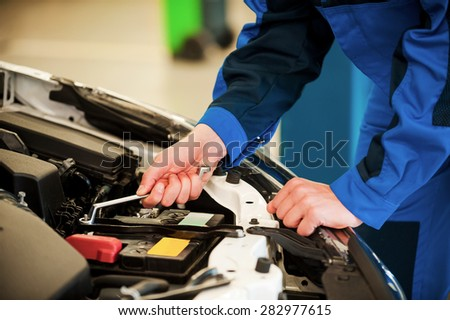 Mechanic at work. Close-up of man in uniform repairing car while standing in workshop - stock photo