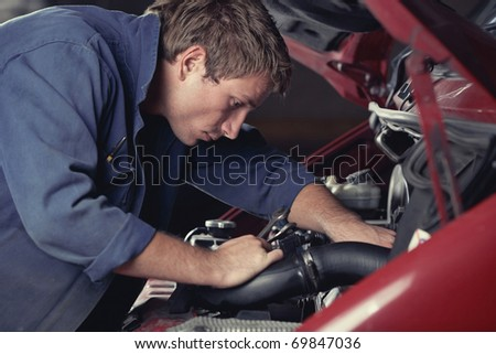 Mechanic at work fixing car in auto service - stock photo