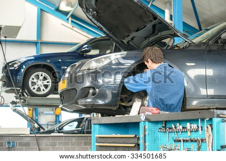 Mechanic, at work on the wheel hub and brake disk of a car in a garage, with other vehicles on car lifts in the background and a trolley with various tools, clamps and wrenches in the foreground.  - stock photo