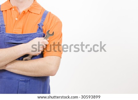 Mechanic at work with a wrench in his hand - stock photo