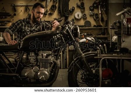 Mechanic building vintage style cafe-racer motorcycle  in custom garage - stock photo