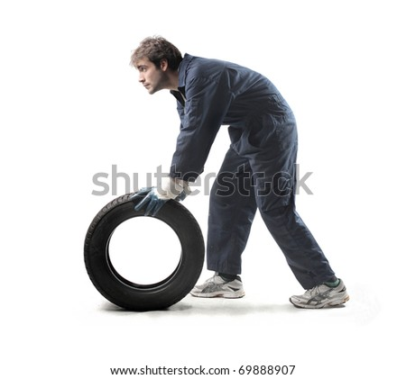 Mechanic carrying a tyre - stock photo