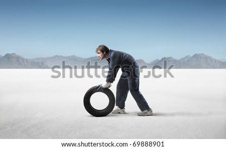 Mechanic carrying a tyre in a desert - stock photo