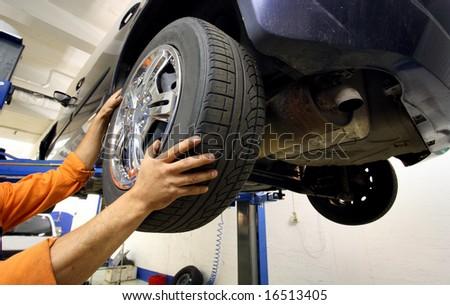 mechanic changing a car wheel. - stock photo